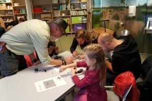 Kinderen zijn druk aan het uilenballenpluizen