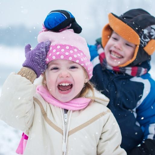 Jongetje en meisje lachend in de sneeuw