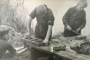 Hans en Gerard maken samen met de kinderen van De Boer zelf bakstenen van gevonden klei.