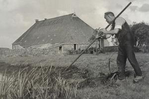 Boerderij Heach Hiem met op de voorgrond een knecht die de sloot met de hand hekkelt.